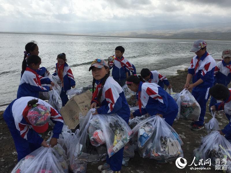 社工组织当地小学生在青海湖畔捡拾垃圾.